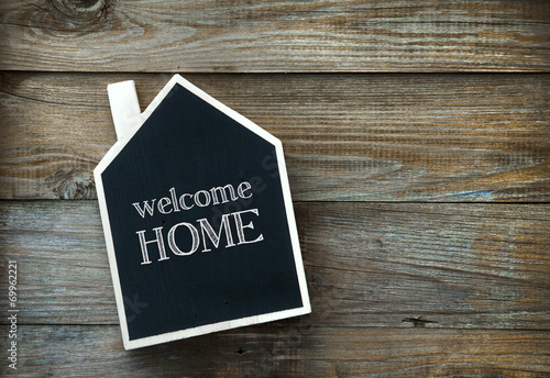 House Shaped Chalkboard sign on rustic wood WELCOME HOME - 69962221
