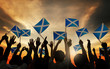 canvas print picture - Group of People Waving Scottish Flags in Back Lit