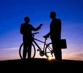 Silhouette of Two man and a Bike