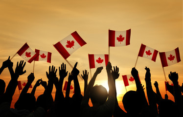 Group of People Waving Flag of Canada in Back Lit
