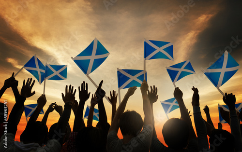 canvas print picture Group of People Waving Scottish Flags in Back Lit