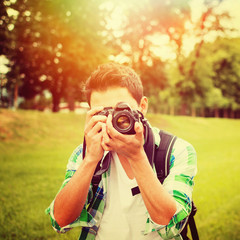 Young male photographer in park on sunny summer day