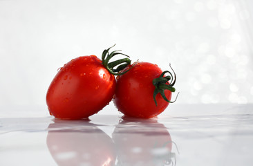 Two red tomatoes with water drops