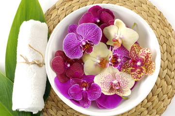 Close up of spa towels, leaf with colorful orchid