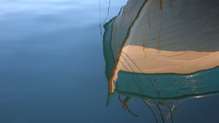 Fishing boat in port with reflections on sea water