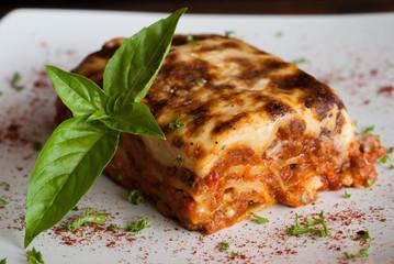 Lasagna on a square white plate