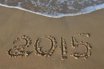 Year 2015 number written on sandy beach