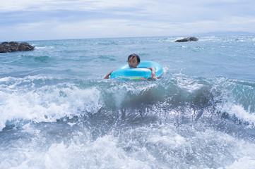 Boy riding a wave in the float