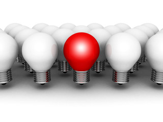 One different red light bulb in row of white ones