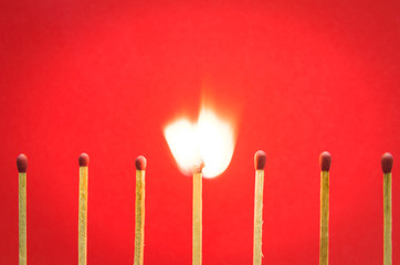 burned match setting on red background for ideas and inspiration
