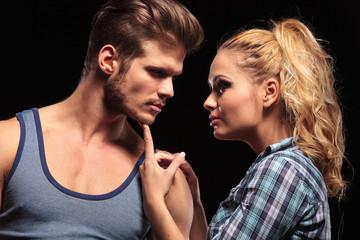 blonde woman holding her boyfriend chin