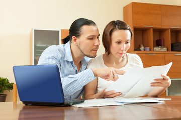 wistful couple calculating budget at home interior