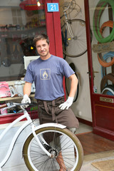 Bike shop owner standing in front of shopwindow