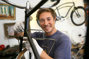Man in workshop fixing bike frame