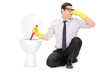 Young man unclogging a stinky toilet with plunger