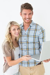Portrait of happy young couple using laptop