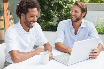 Two friends enjoying coffee together with laptop