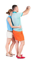Back view of couple photographing.