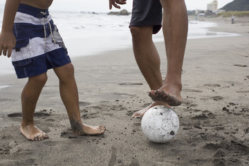 Parent and child to soccer on the beach