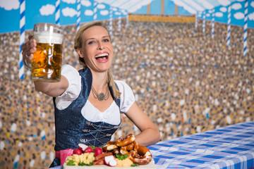 Hübsche Frau im Bierzelt mit Bayrischen Spezialitäten
