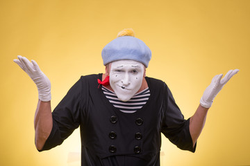 Portrait of male mime isolated on yellow background