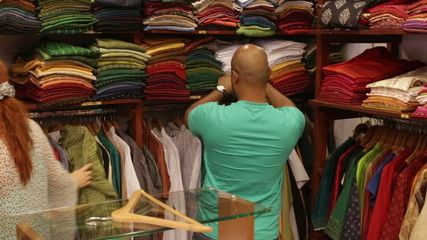 woman chooses clothes in a shop near the shelves