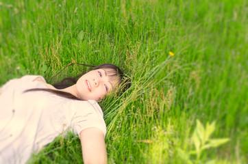 芝生に仰向けになる女性