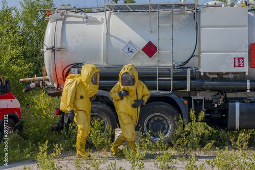 Mans with briefcase in protective hazmat suit - 69977282