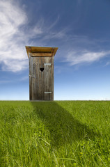 Wooden toilet, green field, blue sky