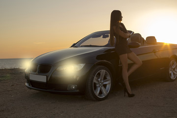 beautiful girl  posing beside a cabriolet on sunset