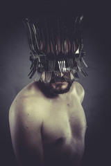 Man with helmet made of forks and knives, concept
