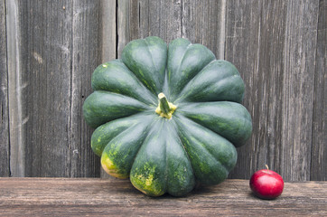 big green pumpkin and small red apple