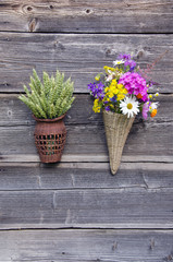 two wicker baskets with flowers and wheat ears on wall