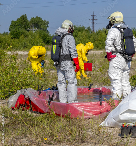 Hazmat team members have been wearing protective suits - 69980088