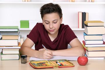 Junge beim Schreiben von Hausaufgaben in der Schule