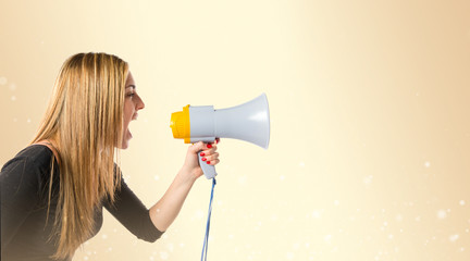 Pretty girl shouting with a megaphone over ocher background