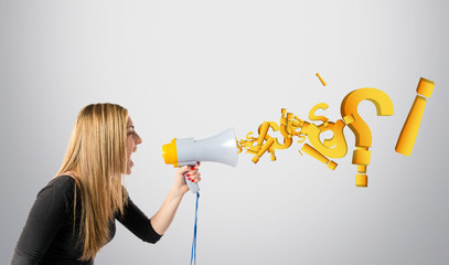 Pretty girl shouting with a megaphone over grey background