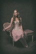 Vintage ballet fashion woman wearing pink corset and dress. Sitt