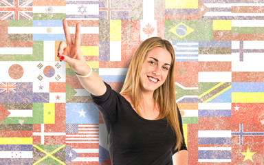 Blonde girl doing victory gesture over flags background