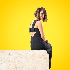 Pretty brunette woman isolated over yellow background