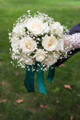 white bouquet in the hands of the bride