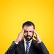 Young businessman with headache over yellow background