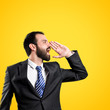 Young businessman screaming over yellow background
