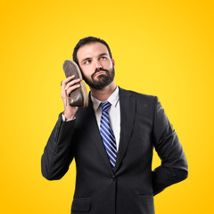 Young businessman talking to his shoe over yellow background