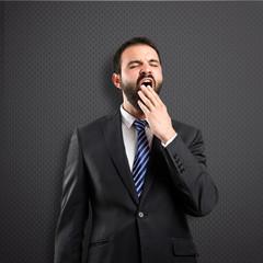 Businessman yawning over black background