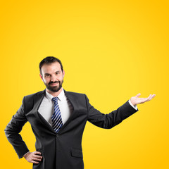 Businessman making showing over yellow background