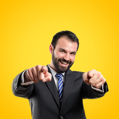 Businessman pointing to the front over yellow background