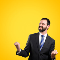 Young business man winner over yellow, background