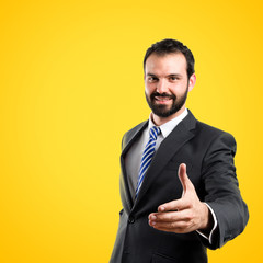 businessman making a deal over isolated yellow background