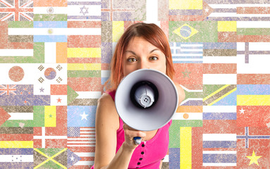Redhead girl shouting with a megaphone over white background